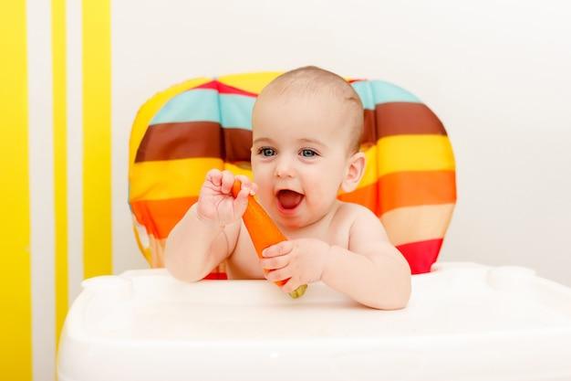 Счастливый маленький ребенок ест морковь Premium Фотографии