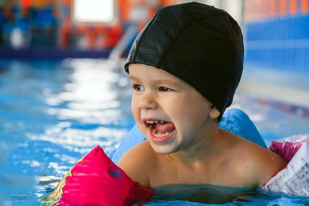Счастливый малыш в черной резиновой шапочке и розовых надувных рукавах смеется и учится плавать Premium Фотографии