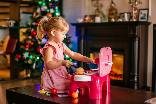 Happy little blonde girl playing near christmas tree with toy kitchen. xmas morning in decorated living room with fireplace and christmas tree. Premium Photo