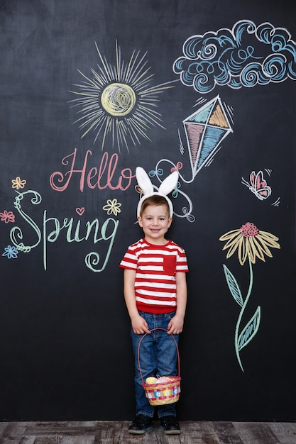 Happy little boy wearing bunny ears and holding easter basket Free Photo