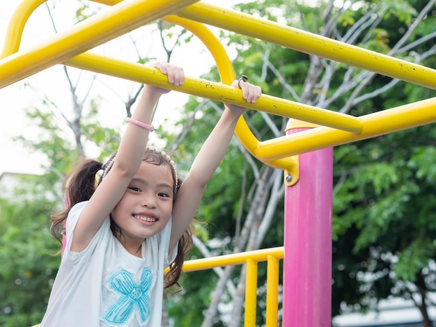 Happy little cute girl 5-6 years old hanging the bar at the playground. Premium Photo