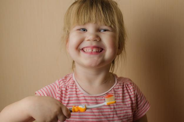 彼女の歯を磨くの幸せな女の子。コピースペース Premium写真