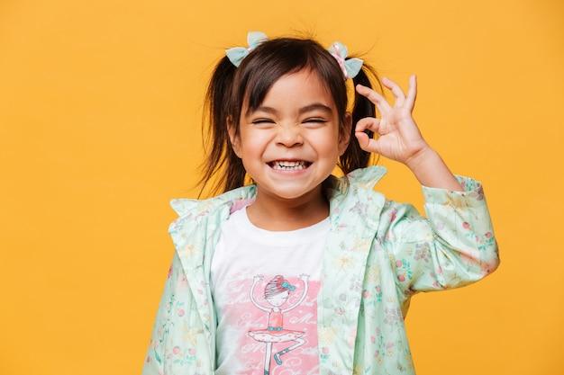 괜찮아 제스처를 보여주는 행복 한 작은 여자 아이. 무료 사진