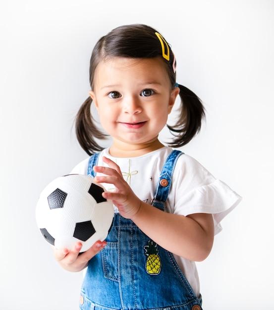 Happy little girl holding a football Premium Photo