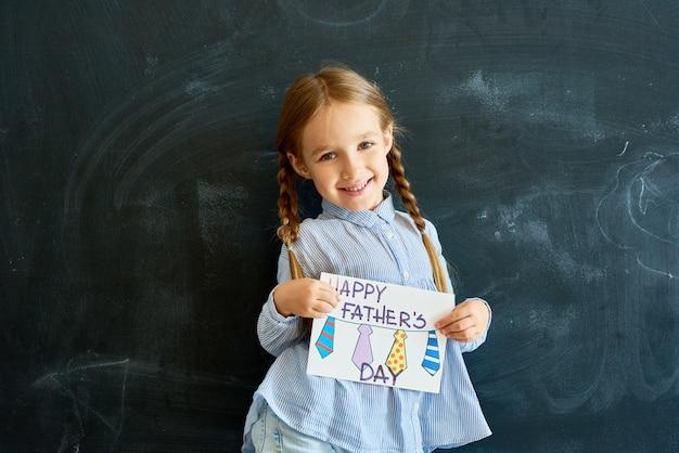 Счастливая маленькая девочка держит открытку на день отцов Premium Фотографии