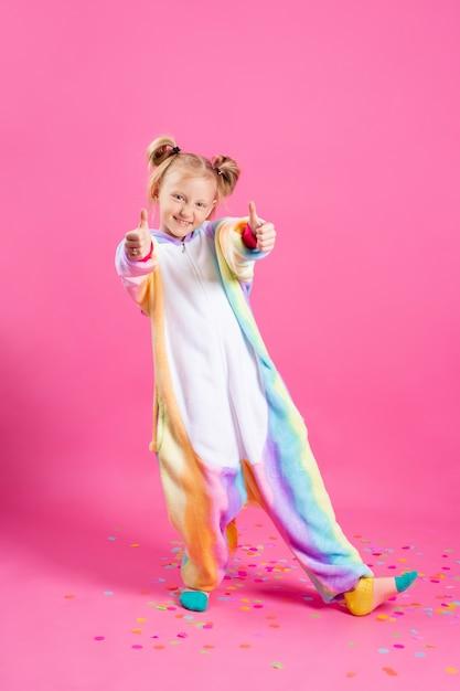 Счастливая маленькая девочка в единороге кигуруми на розовой стене радуется разноцветному конфетти Premium Фотографии