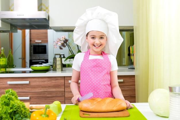 Счастливая маленькая девочка в розовом хлебе резки фартука на кухне. Бесплатные Фотографии