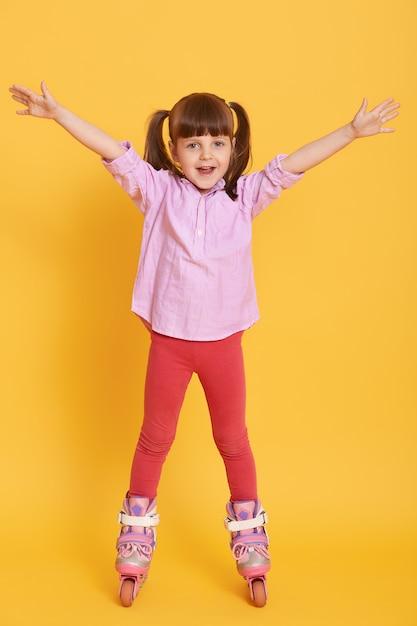 Счастливая маленькая девочка в рубашке и леггинсах с роликовыми коньками позирует в помещении с поднятыми руками Premium Фотографии