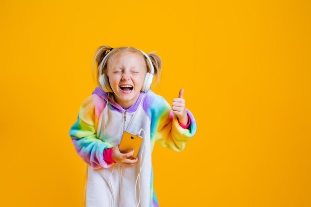 2020 happy-little-girl-kigurumi-unicorn-listens-music-headphones-holding-smartphone_98296-3614.jpg
