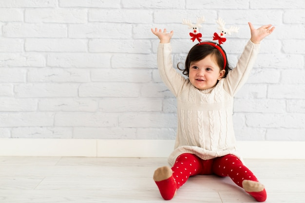 Happy little girl lifting her arms Free Photo
