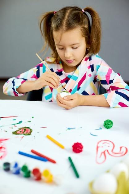 행복 한 어린 소녀 그림, 브러시 계란 집에서 그리기. 부활절을 준비하는 아이, 재미와 축하 잔치. 행복한 부활절, Diy 프리미엄 사진
