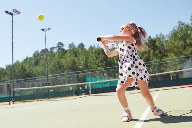 Счастливая маленькая девочка, играя в теннис. летний спорт Бесплатные Фотографии