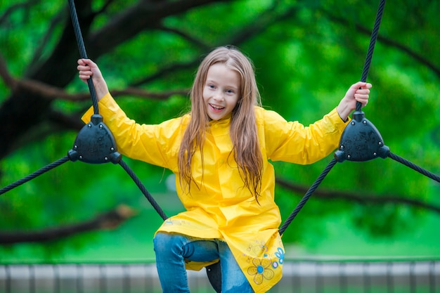 Happy little girl playng on outdoor playground Premium Photo