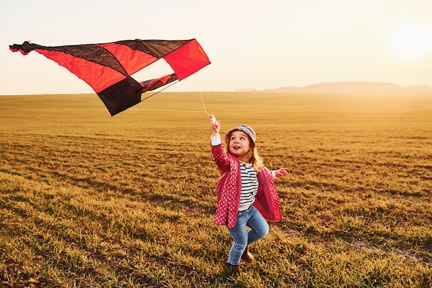 Happy little girl running with kite in hands on the beautiful field at sunrishe time Premium Photo