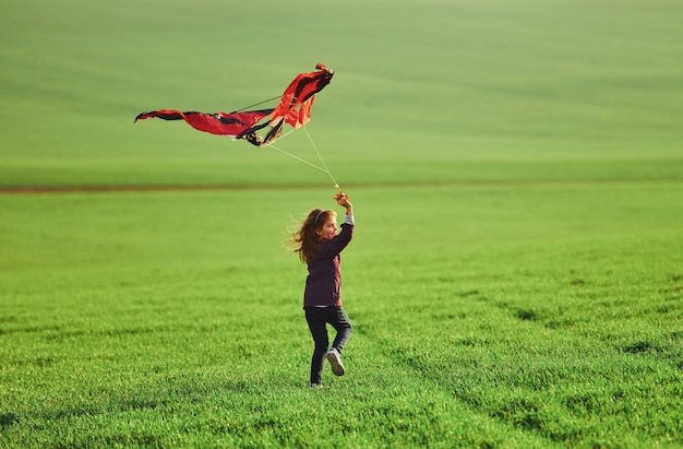 Happy little girl running with kite in hands on the beautiful field Premium Photo