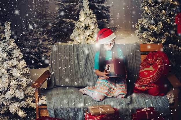 Happy little girl in santa claus hat with present on couch. Premium Photo