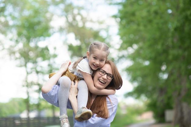 彼女の母親の肩の上に座って、または日当たりの良い夏の日に戻って幸せな女の子 Premium写真