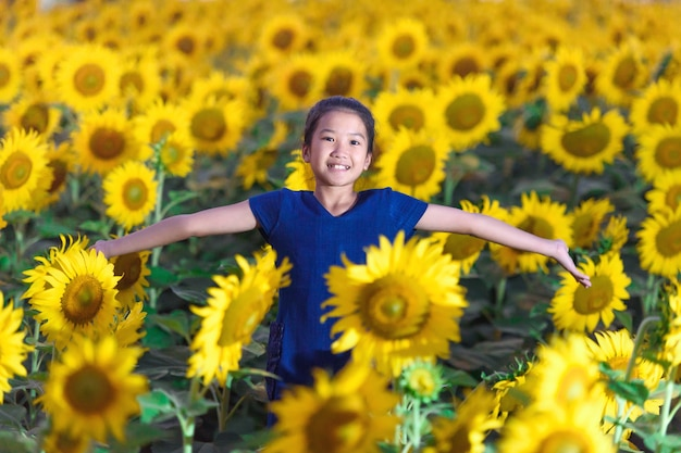 Happy little girl smelling a sunflower on the field Premium Photo