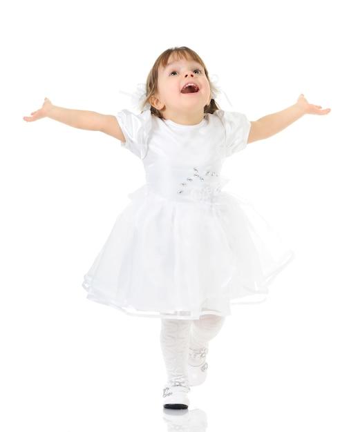 笑顔と白いドレスと靴でポーズをとって幸せな少女、手を広げて、完全な長さの写真の明るい背景 Premium写真