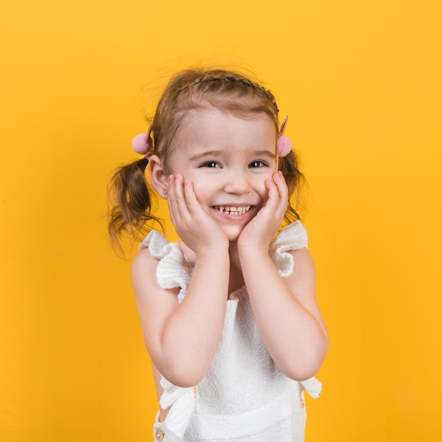 Happy little girl smiling on yellow background Free Photo