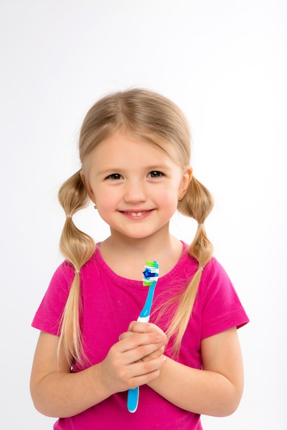 Happy little girl standing with toothbrush isolated on white Premium Photo