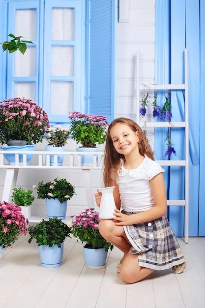 Happy little girl watering flower pots. Premium Photo