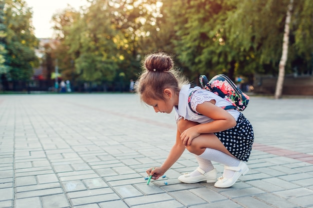Happy little girl wearing backpack and drawing with chalk outdoors primary school. kid having fun after classes Premium Photo
