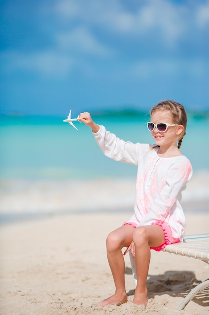 Happy little girl with toy airplane on the beach Premium Photo