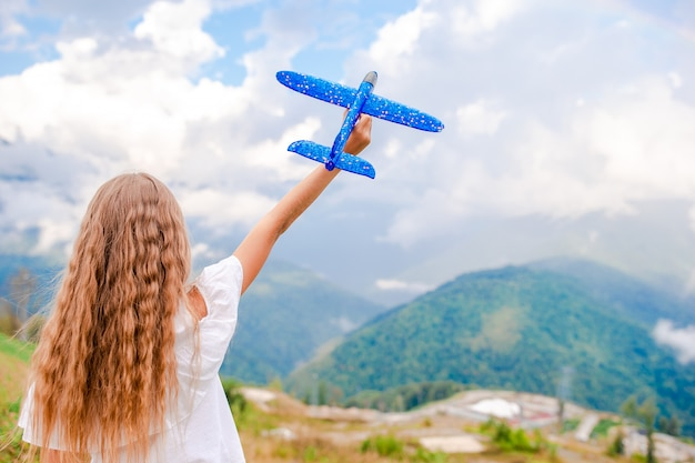 Happy little girl with toy airplane in hands in mountains Premium Photo