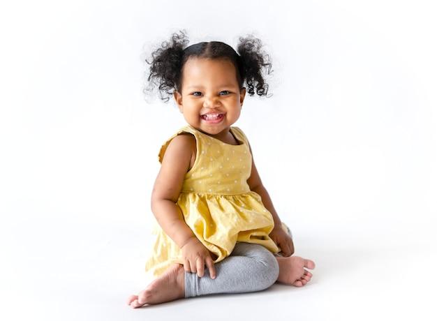 Happy little girl in a yellow dress sitting Premium Photo