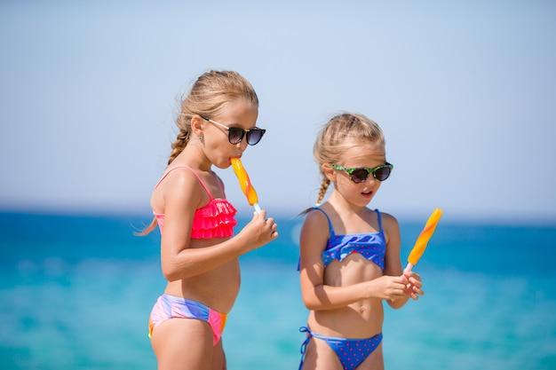 해변 휴가 동안 아이스크림을 먹는 행복 소녀 프리미엄 사진