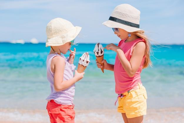 해변 휴가 동안 아이스크림을 먹는 행복 소녀. 프리미엄 사진