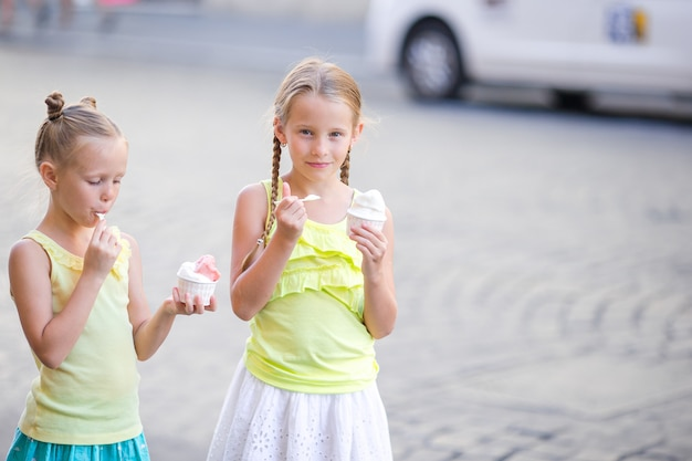 Happy little girls eating ice-creamin open-air cafe. Premium Photo