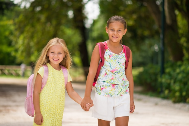 Happy little girls going to school together Premium Photo