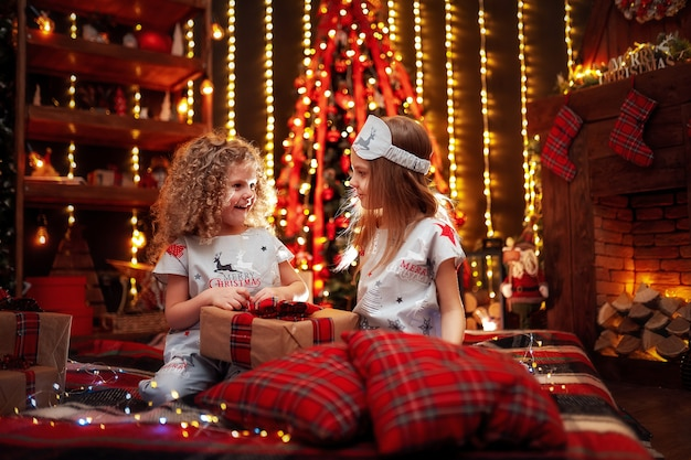 Happy little girls wearing christmas pajamas open gift box by a fireplace in a cozy dark living room on christmas eve. Premium Photo