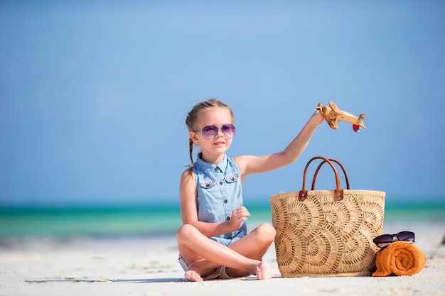 Happy little kid with toy airplane in hands on white sandy beach Premium Photo
