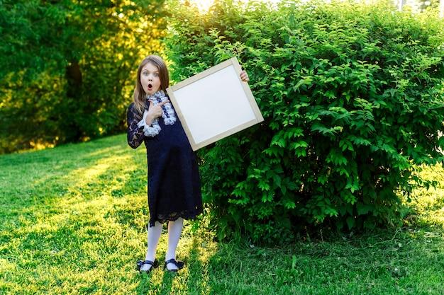 Счастливая маленькая школьница с удивлением указывает на место для текста в рекламе летней школы с местом для текста Premium Фотографии