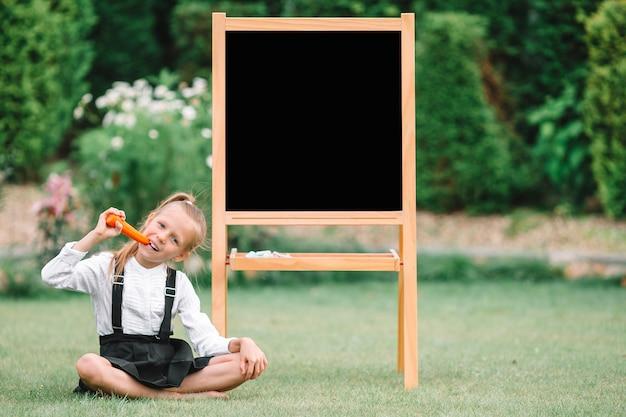 Happy little schoolgirl with a chalkboard outdoor Premium Photo
