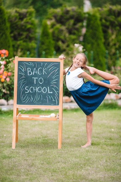 Happy little schoolgirl with a chalkboard outdoor Premium Photo