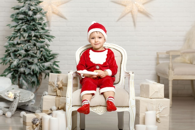 Happy little smiling boy in santa claus costume sitting on armchair near christmas tree and holding christmas gift box Premium Photo