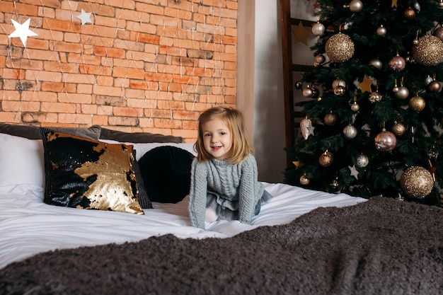 Happy little smiling girl on bed at home. christmas tree Premium Photo