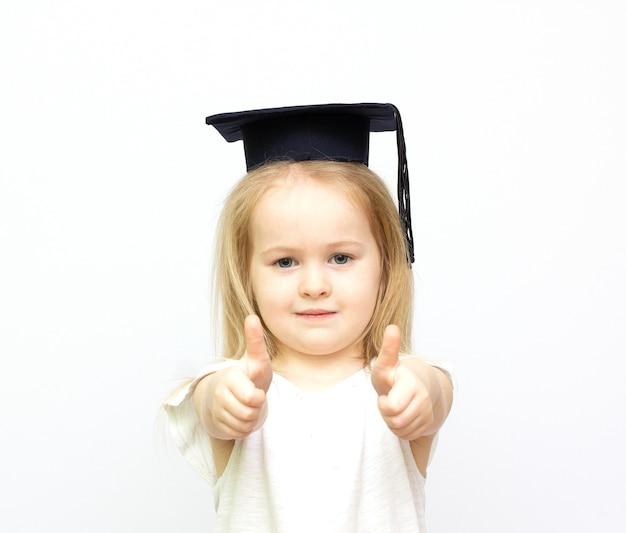 격리 된 흰색 배경에 엄지 손가락을 보여주는 학생 모자에 행복 한 작은 학생 소녀 프리미엄 사진