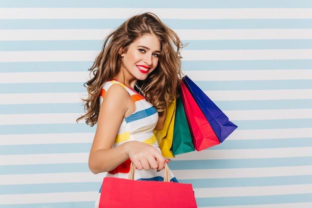 Счастливая длинноволосая женщина улыбается после покупок. портрет довольной белой девушки с бумажными пакетами. Бесплатные Фотографии