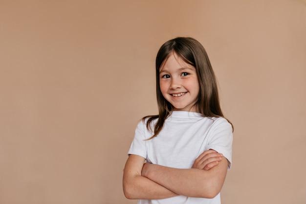 Счастливая привлекательная девушка в белой футболке позирует над бежевой стеной. Бесплатные Фотографии