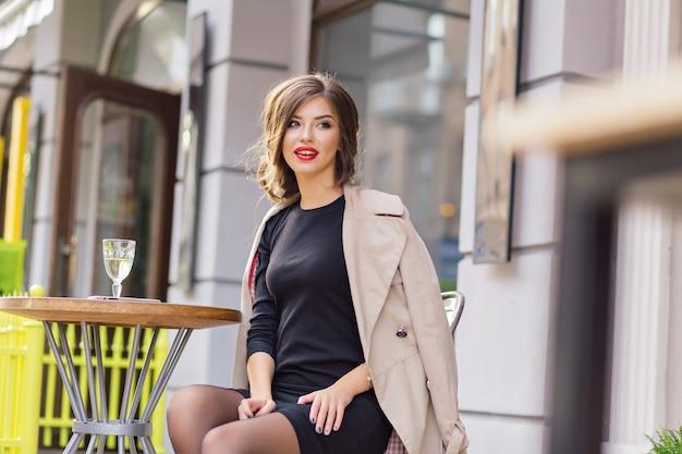 黒のドレスとベージュのコートを着た幸せな愛らしい女性が屋外のカフェテリアに座って、グラスワインで休んでいます 無料写真