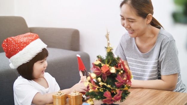 Happy lovely asian girl decorating ornament on christmas tree with her mother Premium Photo