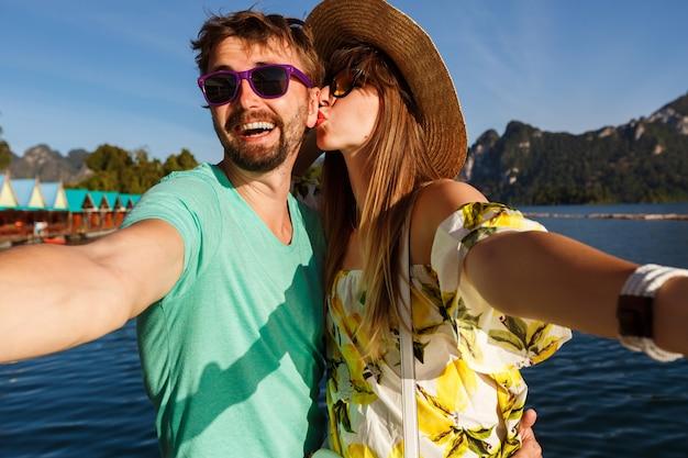Счастливая милая пара, делающая селфи на отдыхе на горах и озере, летняя яркая одежда, шляпа и солнцезащитные очки, поцелуи и веселье вместе. Бесплатные Фотографии