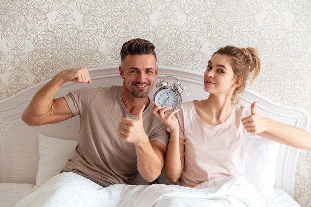 Happy lovely couple sitting together on bed with alarm clock Free Photo