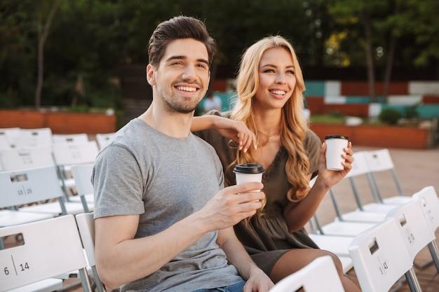 椅子に一緒に座って、屋外でコーヒーと一緒に映画を見ている幸せな素敵な若いカップル Premium写真
