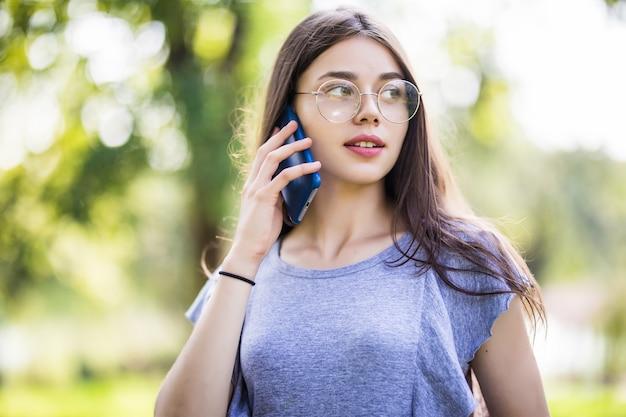 Felice bella giovane donna in piedi e parlando al cellulare in città Foto Gratuite
